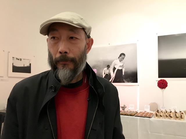 Le photographe chinois Mo Yi, devant des œuvres de Lee Gap Chul